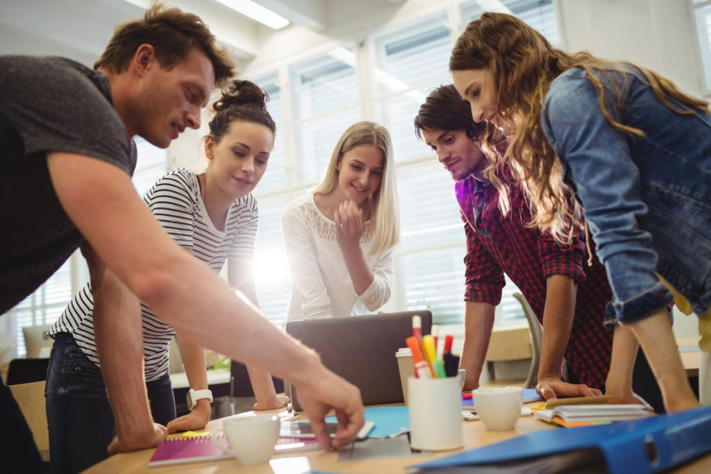 Pessoas em volta de uma mesa de trabalho, usando a comunicação assertiva