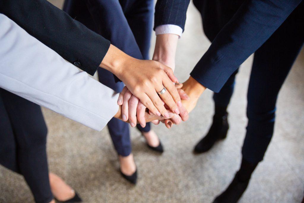 mulheres inspiradoras unidas com as mãos sobrepondo umas das outras