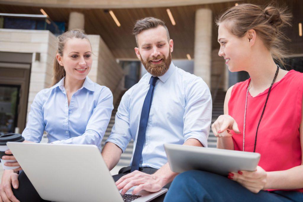 três profissionais reunidos discutem sobre um serviço realizado e mostram a importância da comunicação nas organizações